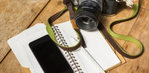 Photo of a note pad, pen, and camera on a wooden table illustrate the nonprofit story collecting tool.