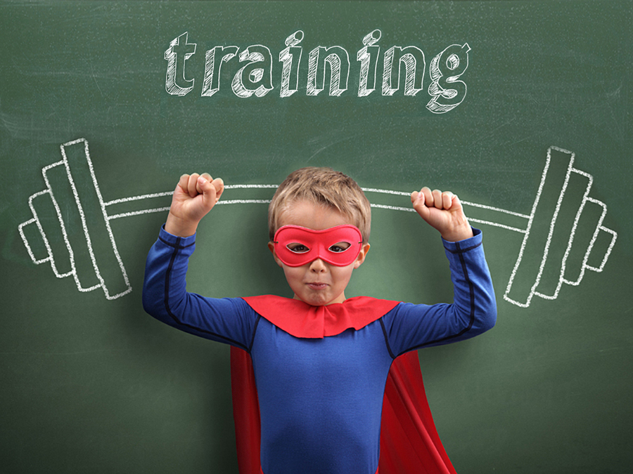 Boy in superman costume posing in front of chalkboard with image of huge barbell as illustration of nonprofit communications training